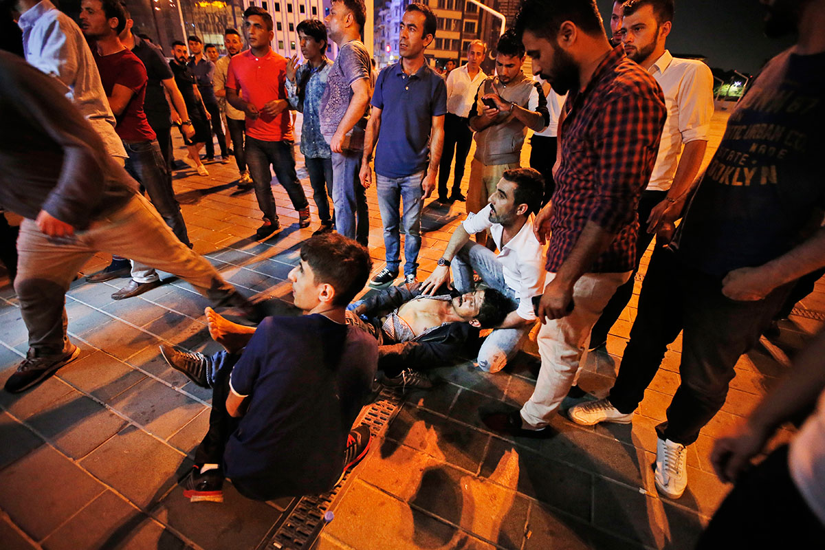 Anticoup protesters attend to a man who was wounded by gunfire in Istanbul's Taksim square