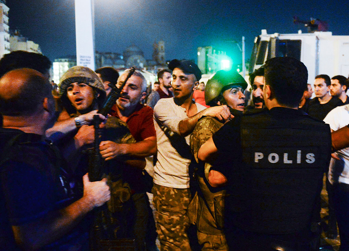 Turkish soldiers, held by civilians, are handed to police officers in Taksim square