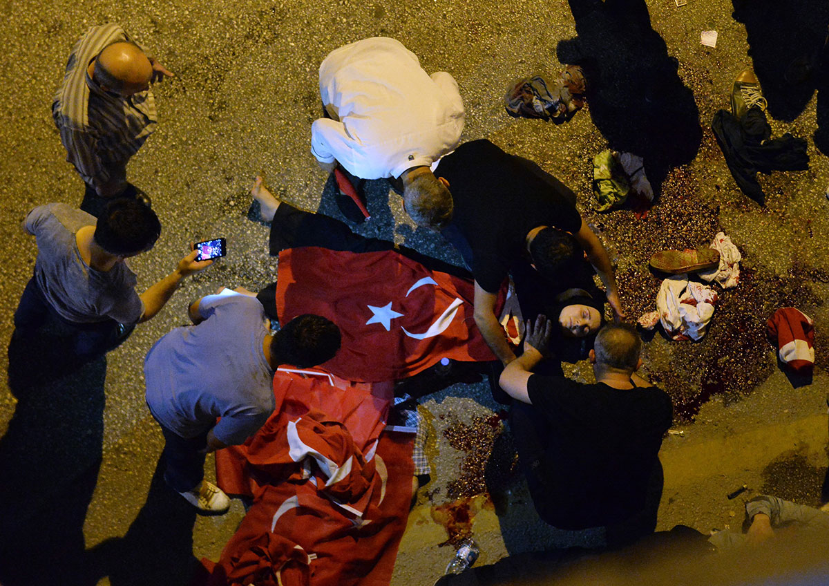 A wounded woman draped in a Turkish flag is checked by others near military headquarters in Ankara.